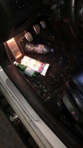 A l'avant d'une voiture, côté conducteur, des éclats de verre se trouvent au niveau des pédales. Trois bouteilles en plastiques jonchent également le sol.